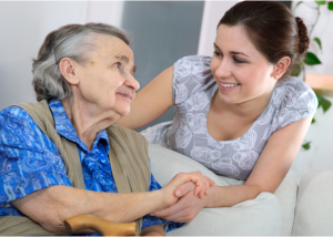 senior and caregiver looking at each other smiling